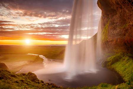 the cascade: Seljalandsfoss es una de las m�s bellas cascadas de la Islandia. Se encuentra en el sur de la isla. Esta foto est� tomada en la incre�ble puesta de sol en aprox. 1 am. Foto de archivo