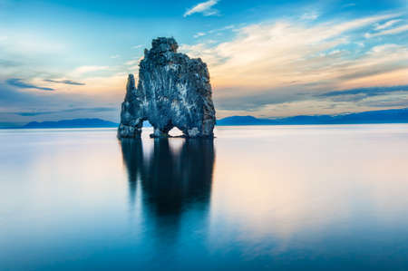 Hvitserkur è una roccia spettacolare nel mare, sulla costa settentrionale dell'Islanda. Leggende dicono che è un troll pietrificato. Su questa foto Hvitserkur riflette nell'acqua di mare dopo il tramonto del sole a mezzanotte.