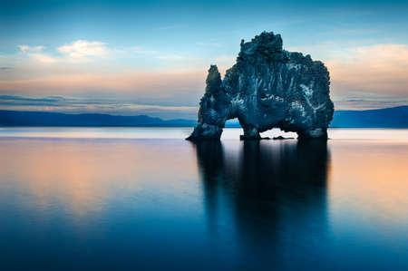 Hvitserkur est une roche spectaculaire dans la mer sur la côte nord de l'Islande. Les légendes disent que c'est un troll pétrifié. Sur cette photo Hvitserkur reflète dans l'eau de mer après le coucher du soleil de minuit.