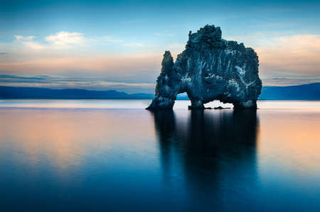 after midnight: Hvitserkur is a spectacular rock in the sea on the Northern coast of Iceland. Legends say it is a petrified troll. On this photo Hvitserkur reflects in the sea water after the midnight sunset.
