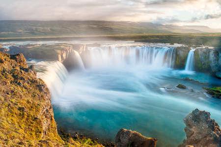 flujo: Godafoss es una cascada muy hermosa islandesa. Se encuentra en el norte de la isla, no lejos del lago Myvatn y la carretera de circunvalaci�n. Esta foto se toma despu�s de la puesta del sol de medianoche con una larga exposici�n Foto de archivo