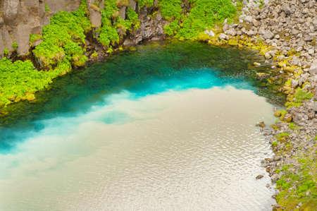 afflux: Eau de source claire et propre de la montagne est m?lang? avec de l'eau sale de la rivi?re sauvage glaciaire Jokulsa un Fj?llum en Islande Banque d'images