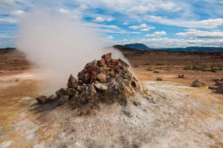 fumarole: Fumarola en el Hverir ?rea geot?rmica, Islandia. La zona que rodea es multicolor y agrietada.