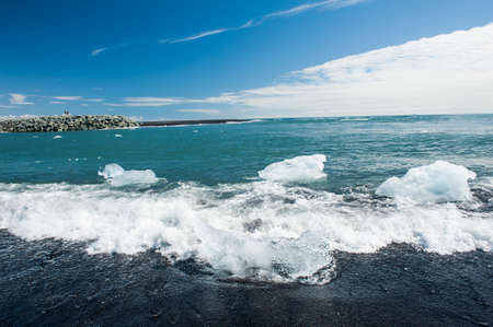Beautiful beach in the South of Iceland with a black lava sand is full of icebergs washed by the sea photo