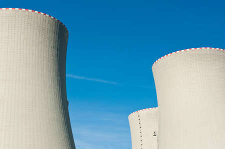 nuclear reactor: Nuclear power plant cooling towers against a blue sky Stock Photo