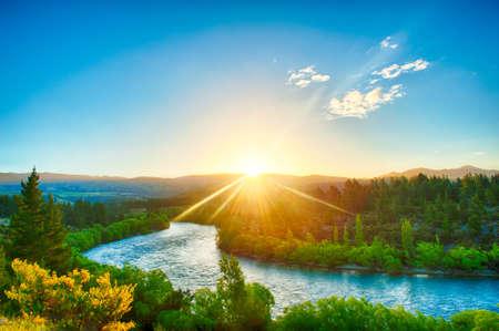 sol: Por do sol bonito sobre a curva do rio Clutha, Nova Zel Imagens
