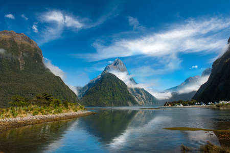 fiordland: Famous Mitre Peak rising from the Milford Sound fiord and reflecting in water. Fiordland national park, New Zealand