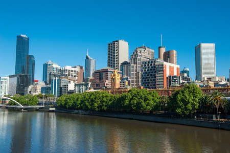 Melbourne skyline with skyscrapers and famous Flinders Streert train station seen across the river Yarra. Victoria, Australia photo