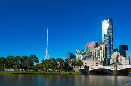 river banks: Melbourne skyline with skyscrapers and famous  Melbourne Arts Centre Spire seen across the river Yarra. Victoria, Australia Stock Photo