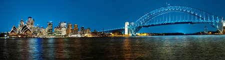 Panoramische foto van Sydney skyline met Harbour Bridge in de avond na zonsondergang