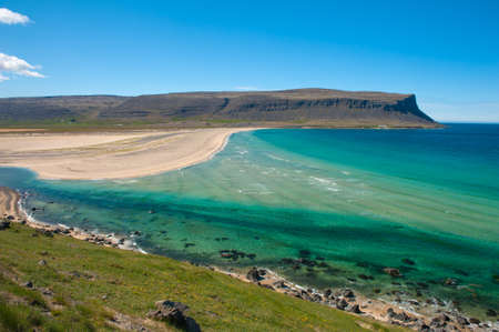 Extremly beautiful bay with mighty golden beaches and turquise sea in the West Fjords, Iceland. photo