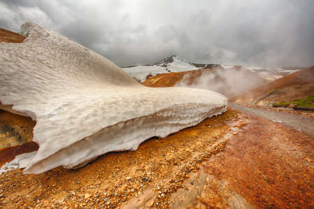 mud and snow: Iceland is a land of ice and fire. In the geothermal area Kerlingarfjoll one can see smoke and boiling fumaroles from the geothermal field as well as mountains covered by ice and snow. Stock Photo