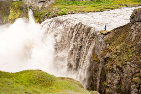 Unrecognizable photographer is taking pictures of Hafragilsfoss, very powerful waterfall. It is located in Jokulsargljufur National Park the northeasten Iceland on the river Jokulsa a Fjollum. photo