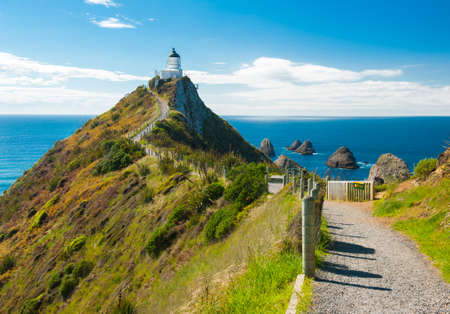 Lighthouse on Nugget Point. It is located in the Catlins area on the Southern Coast of New Zealand, Otago region. The Lighthouse is surrounded by small rock islands, nuggets photo