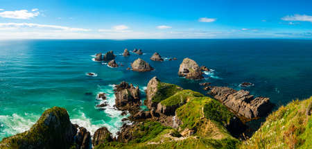 Nugget Point is located in the Catlins area on the Southern Coast of New Zealand, Otago region. The area is famous for many rock islands - nuggets - in the sea. Panoramic photo photo