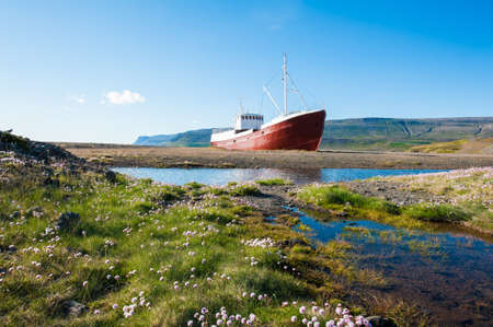 fjords: Old fishing boat that shipwrecked in one of the fjords of the Iceland in the Westfjords  Stock Photo