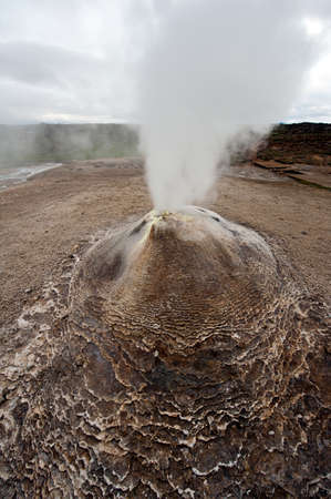 Fumarole in the geothermal area Hveravellir, central Iceland. The area around is layered and cracked.  photo
