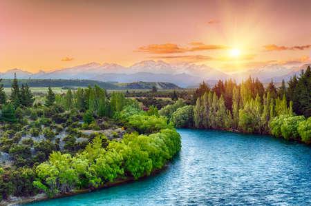 Hermosa puesta de sol sobre la curva del río Clutha con picos de los Alpes del Sur en el horizonte, Nueva Zelanda