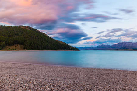 new scenery: Beautiful dramatic sunset over the incredibly blue lake Tekapo with mountains, Southern Alps, on the horizon. New Zealand Stock Photo