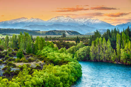 new horizon: Beautiful sunset over the bend of the river Clutha with Southern Alps peaks on the horizon, New Zealand Stock Photo