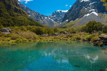 snowcapped: Gertrude Saddle with a snowy mountains and a turquoise lake, Fiordland national park, New Zealand South island