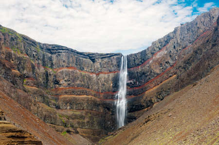 rock layers: Hengifoss is the second highest waterfall on Iceland. It is located on the East on the island. Perhaps the most special thing about the waterfall are multicolored layers in the basalt rock behind the waterfall Stock Photo