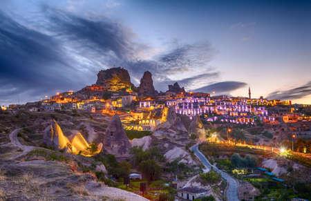 pavo: Ciudad antigua y un castillo de Uchisar cavaron desde una montaña después del crepúsculo, en Capadocia, en Turquía Foto de archivo
