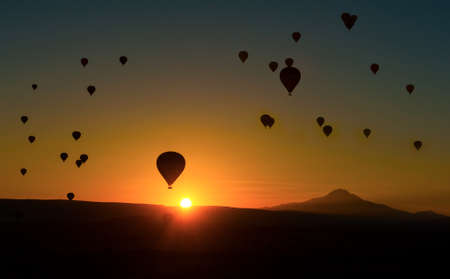 Silhouetts of hot balloons in morning sunrise and a mountain Erciyes. Cappadocia, Turkey photo