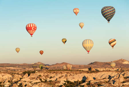 Hot air balloons flying over Cappadocia near Goreme at sunrise, Turkey photo