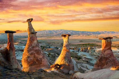 goreme: Rocks looking like mushrooms dramatically lit by a sunset in Cappadocia, Turkey