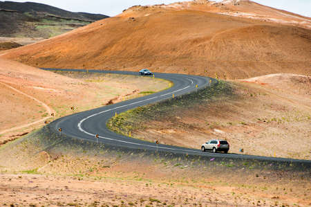 s curve: Road with cars leading through the mountain landscape looks like a big symmetric S letter, Iceland.