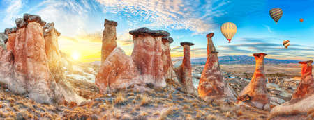 dramatically: Rocks looking like mushrooms dramatically lit by a sunset in Cappadocia, Turkey. With balloons