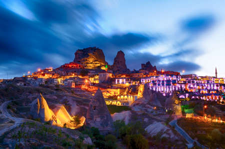 Ancient town and a castle of Uchisar dug from a mountains after twilight, Cappadocia, Turkey photo