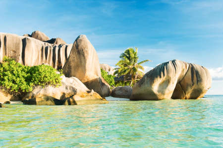 Beautifully shaped granite boulders reflecting in the water at Anse Source dArgent beach, La Digue island, Seychelles photo