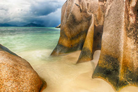 d argent: Beautifully shaped granite boulder in the sea of Seychelles at Anse Source dArgent beach taken with a long exposure. Dramatic stormy sky