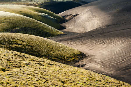 contrasty: A contrasty wavy landscape of a former brook where black volcanic dunes meet green dunes covered by moss. Lakagigar volcanic area, Iceland. Sunset time Stock Photo