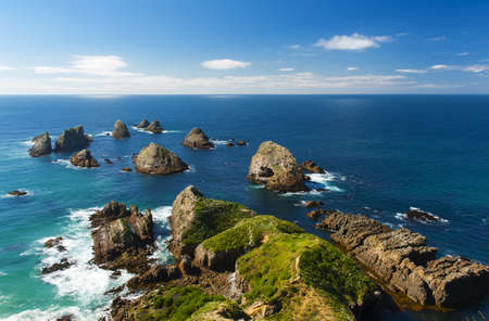 south island new zealand: Nugget Point is located in the Catlins area on the Southern Coast of New Zealand, Otago region. The area is famous for many rock islands - nuggets - in the sea. Stock Photo