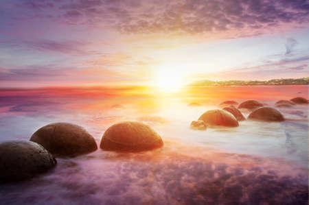 new zealand beach: Moeraki Boulders on the Koekohe beach, Eastern coast of New Zealand. Sunset and long exposure
