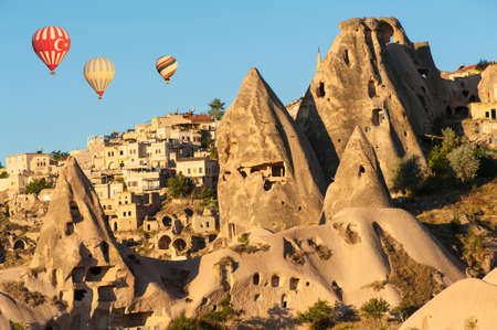Hot air balloons flying over Cappadocia near Uchisar castle at sunrise, Turkey photo