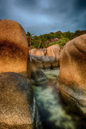 d argent: Beautifully shaped granite boulders in the sea of Seychelles at Anse Source dArgent beach taken with a long exposure. Dramatic stormy sky at sunset time Stock Photo