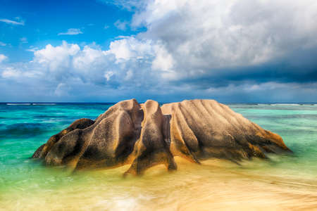 argent: Beautifully shaped granite boulder is washed by sea at Anse Source dArgent beach, La Digue island, Seychelles. Long daytime exposure