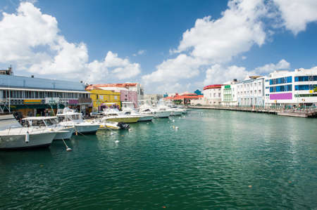Main water canal with ships and shops in Bridgetown capital of Barbados. Caribbean