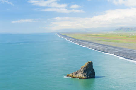 Black sandy beach seen from the cliff at the cape Dyrholaey, the most southern point of Iceland.