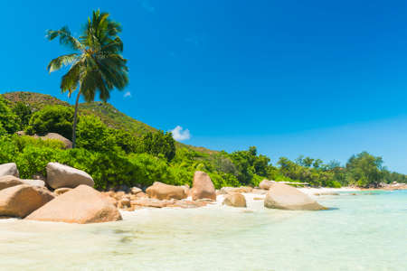 beach panorama: Beautiful beach Anse Takamaka seen from the granite boulders, La Digue island, Seychelles. Panorama