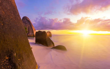 d'argent: Beautifully shaped granite boulders and a dramatic sunset  at Anse Source dArgent beach, La Digue island, Seychelles Stock Photo