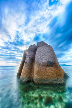 anse source d argent: Beautifully shaped granite boulder in the sea of Seychelles at Anse Source dArgent beach taken with a long exposure. Stock Photo