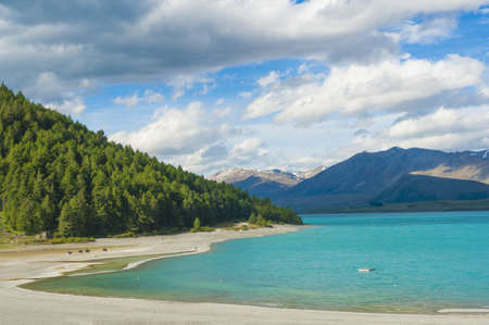 to the other side: Beautiful incredibly blue lake Tekapo with mountains, Southern Alps, on the other side. New Zealand