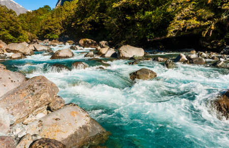 fiordland: Beautiful turquoise creek with snowy peaks near the Milford highway. Fiordland National Park, New Zealand Stock Photo