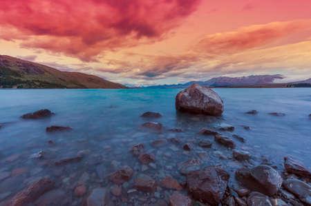 lake sunset: Beautiful dramatic sunset over the incredibly blue lake Tekapo with mountains, Southern Alps, on the horizon. New Zealand Stock Photo