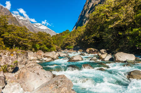 creek: Beautiful turquoise creek with snowy peaks near the Milford highway. Fiordland National Park, New Zealand Stock Photo